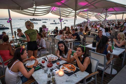 Gente comiendo en una terraza con vistas al mar